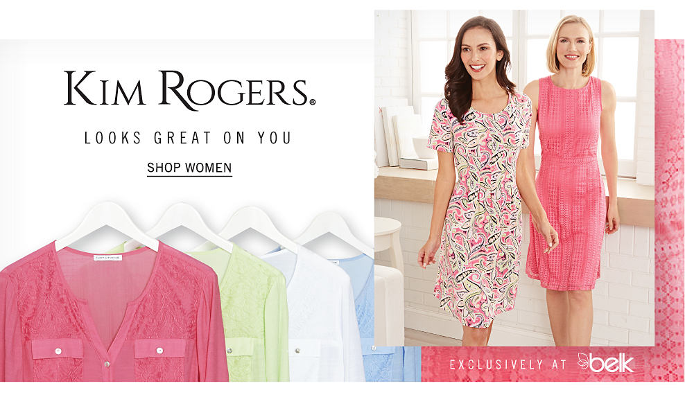 An assortment of long sleeved button front blouses in a variety of colors hanging on white hangers. A woman wearing a multi colored print short sleeved dress standing next to a woman wearing a pink sleeveless dress. Kim Rogers. Looks great on you. Shop women.