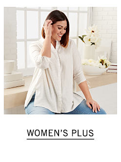 A woman wearing a white long sleeved button front blouse & blue jeans. Shop women's plus.