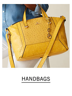 A woman wearing a light blue blouse & white pants carrying a yellow leather handbag. Shop handbags.