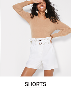 A woman in white shorts and a beige top. Shop shorts.