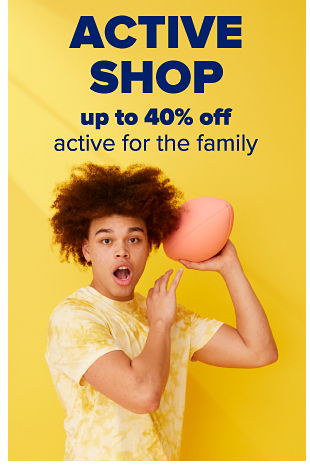 A young man wearing a yellow tie-dye top and throwing a football. Active Shop. Up to 40% off active for the family.