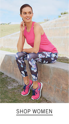 A woman wearing a fuchsia tank top, multi colored print pants & fuchsia sneakers. Shop women.