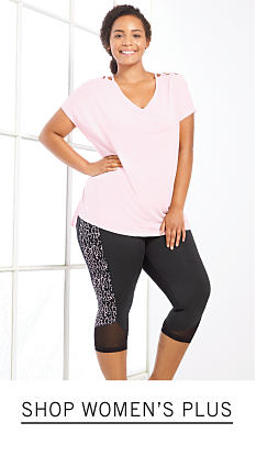 A woman wearing a light pink tee & black pants. Shop women's plus.