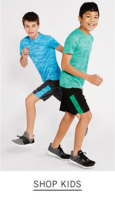 A boy wearing a light blue T shirt, navy shorts with a teal stripe on the side & black sneakers standing next to a boy wearing a green T shirt, black shorts with a green stripe on the side & black sneakers. Shop kids.