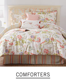 A bed with floral bedding and pillows to match. Shop comforters.