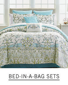 A bed with printed bedding and pillows to match. Shop bed in a bag sets.