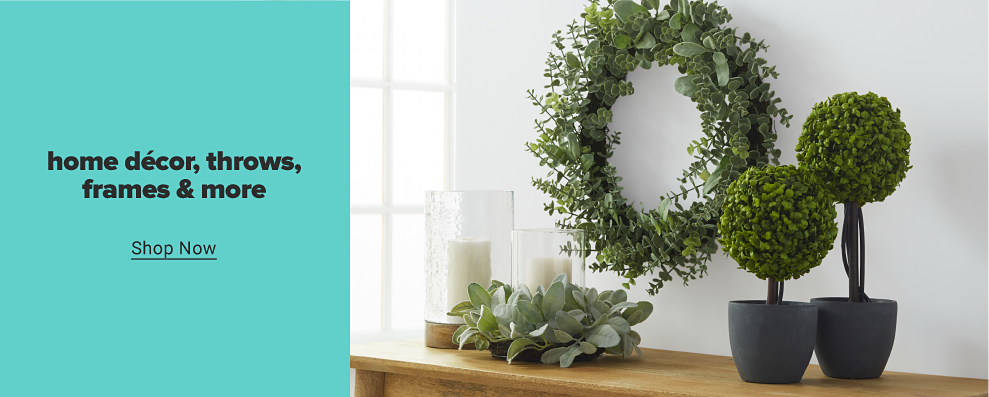 An artificial wreath made of greenery hangs on a white wall. Below the wreath are two white candles in glass vases featuring wood trim and greenery around the bases. Two mini artificial trees sit in small black pots. Home decor, throws, frames and more. Shop now.