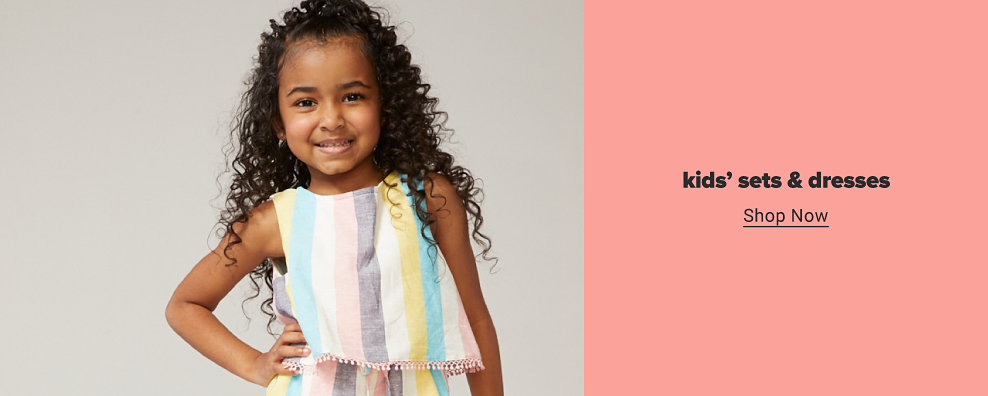 A little girl in a vertical striped tank top with tassel accents along the hem and matching shorts. Kids sets and dresses. Shop now