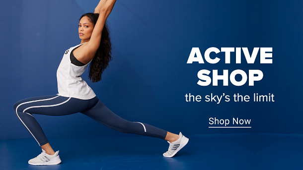 A woman wearing white sneakers, blue leggings and a white tank top with an Adidas logo across the chest. She is in a warrior yoga pose. Active shop. The sky's the limit. Shop now.