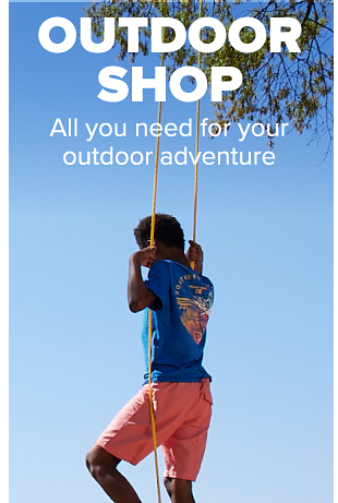 A boy wearing a blue, graphic tee and coral shorts swings from a tree. Outdoor shop. All you need for your outdoor adventure.