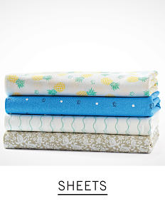 A stack of folded sheets in a variety of prints. Shop sheets.