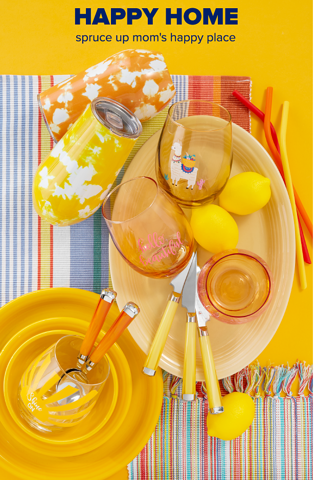An assortment of yellow dinnerware and serveware sits atop multi-colored, striped placemats. Yellow and orange tie-dye tumblers. Four summer-themed, stemless wine glasses. Orange and yellow cutlery and straws. Happy Home. Spruce up mom's happy place.