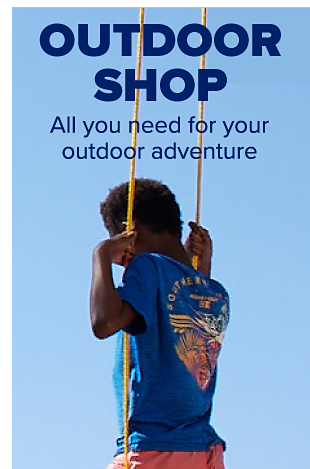 A little boy swings from a tree and he is wearing a blue graphic tee and coral swim shorts. Outdoor shop. All you need for your outdoor adventure.