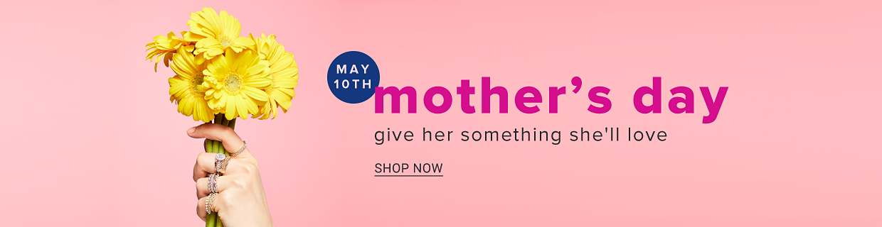 A woman's hand holding yellow flowers. May 10th, mother's day. Give her something she'll love. Shop now.