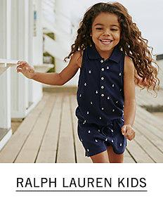 A girl wearing a navy sleeveless dress with a white dot print. Shop Ralph Lauren Kids.
