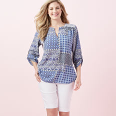 A woman wearing a blue & white print long sleeved top & white capris. Shop Kim Rogers.
