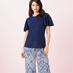 A woman wearing a navy short sleeved top & blue & white patterned print pants. Shop New Directions.
