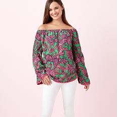 A woman wearing a fuchsia & green paisley print cold shoulder long sleeved top & white pants. Shop Crown & Ivy.