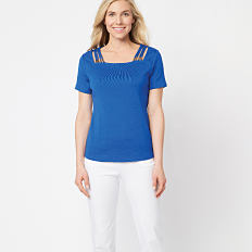 A woman wearing a blue short sleeved top & white pants. Shop Rafaella.