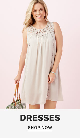 A woman wearing an off white sleeveless dress with lace neckline detail. Dresses. Shop now.