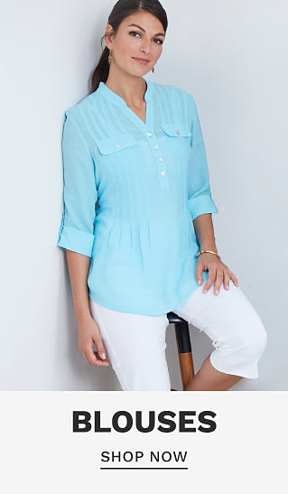 A woman wearing a light blue long sleeved button front blouse. Blouses. Shop now.