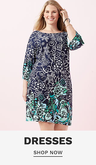 A woman wearing a multi colored floral print long sleeved dress. Dresses. shop now.
