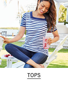 7e42eb4f4 A woman wearing a blue   white horizontal striped short sleeved top   blue  jeans.