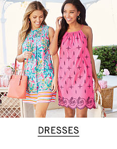 1723510d1ade71 A woman wearing a multi colored print sleeveless dress standing next to a  woman wearing a