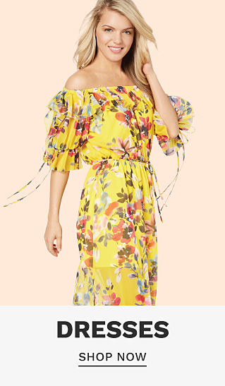 A woman wearing a yellow cold shoulder short sleeved dress with a multi colored floral print. Dresses. Shop now.