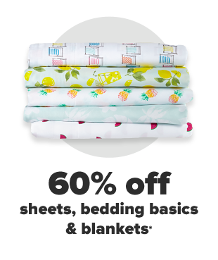 Folded sheets of different colors in a brown wicker basket. 60% off sheets, bedding and blankets.