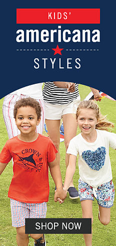 A boy wearing a red T shirt with a black front fishing graphic & red, white & blue shorts standing next to a girl wearing a white tee with a multi colored heart front graphic & multi colored shorts. Kids Americana Styles. Shop now.