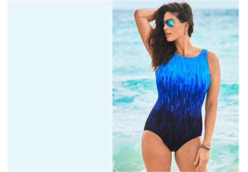 A woman wearing a black & brown one piece swimsuit. Long Torso. Solutions for the perfect fit. Shop now.