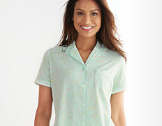 A woman wearing a light green short sleeved button front pajama top. Shop tops.