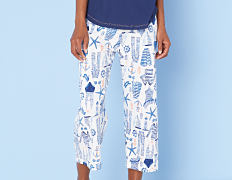 A woman wearing a blue short sleeved pajama top & blue & white patterned print pajama bottoms. Shop bottoms.