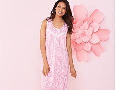A woman wearing pink & white print sleeveless nightgown. Shop nightgowns.
