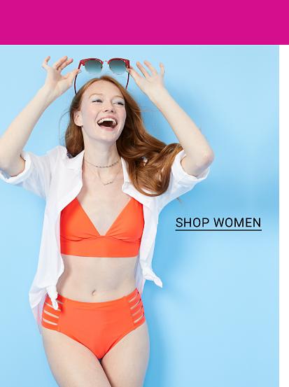 Swimwear for the family. A woman in an orange bikini, a white open front top and sunglasses, shop women.