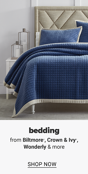 A bed with a navy quilt and pillows to match. Bedding from Biltmore, Crown and Ivy, Wonderly and more, shop now.