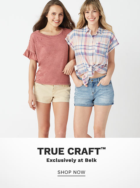 A young woman wearing a short sleeved dusty rose top & beige shorts standing next to a multi colored plaid short sleeved button front blouse & denim shorts. True Craft. Exclusively at Belk. Shop now.