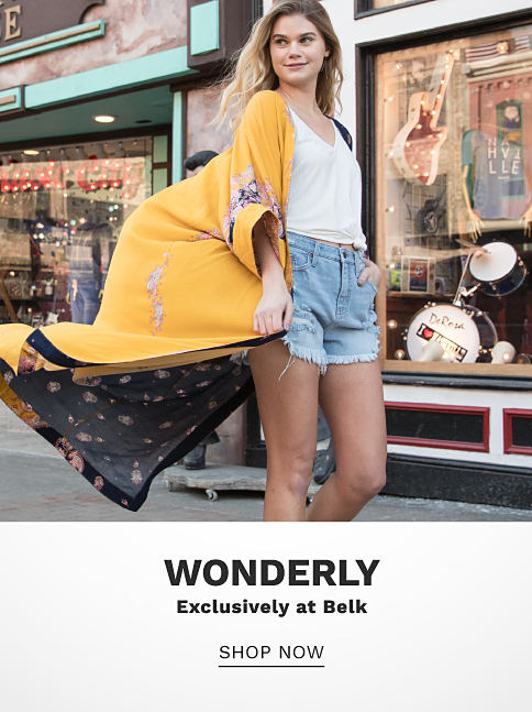 A young woman wearing a long yellow jacket with a multi colored interior print, a white top & denim shorts. Wonderly. Exclusively at Belk. Shop now.