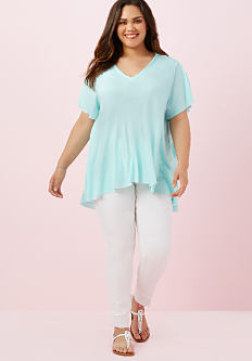 A young woman wearing a light blue short sleeved top, white pants & white strappy sandals. Shop tops.
