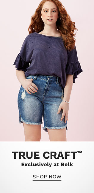 A young woman wearing a blue - gray short sleeved top & denim shorts. True Craft. Exclusively at Belk. Shop now.