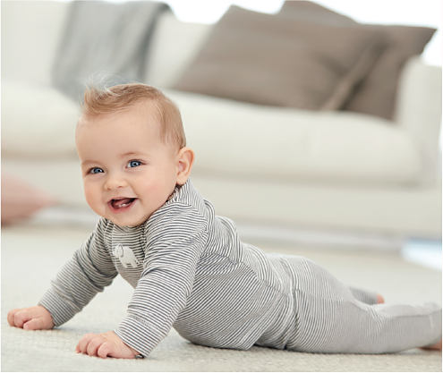 A baby wearing a black & white horizontal striped onesie. Carters. Little Baby Basics.