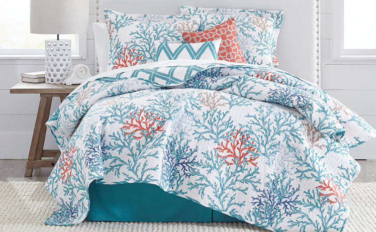 A bed made with a teal, white and peach coral reef pattern comforter and matching pillows.