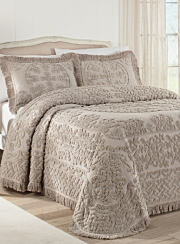 A beige bedspread and matching pillows on a bed. Shop bedspreads and coverlets.