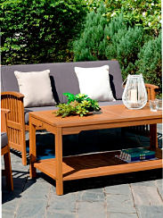 An outdoor couch with throw pillows and an outdoor coffee table. Shop furniture.