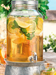 A glass iced tea dispenser on a metal pedestal. Shop summer drinkware.
