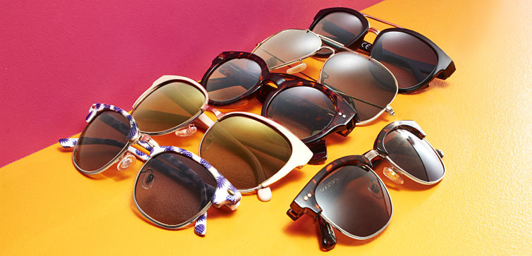 A collection of sunglasses against a yellow and pink background.