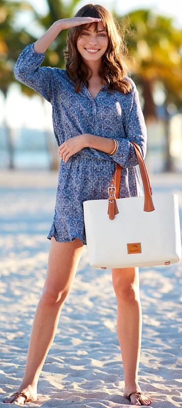 A woman standing on a beach holding a cream Dooney & Bourke handbag.