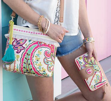 A woman carrying a brightly colored Spartina 449 handbag and wallet.
