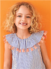 A girl wearing a striped top with a ruffle neck and tassels. Shop Girls 4-6X.